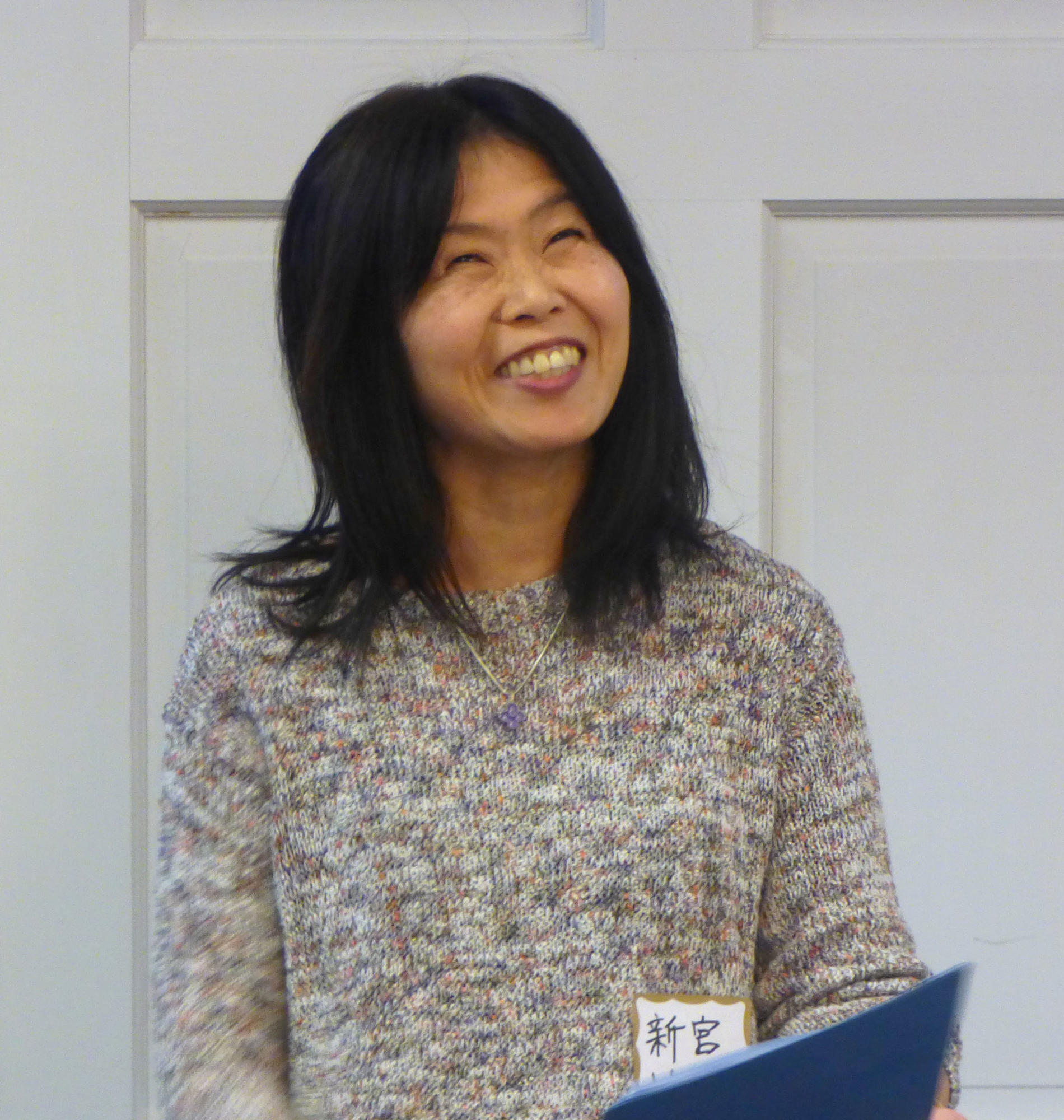 Ikue Shingu, wearing a cream-colored sweater, throws her head back and laughs while delivering her speech