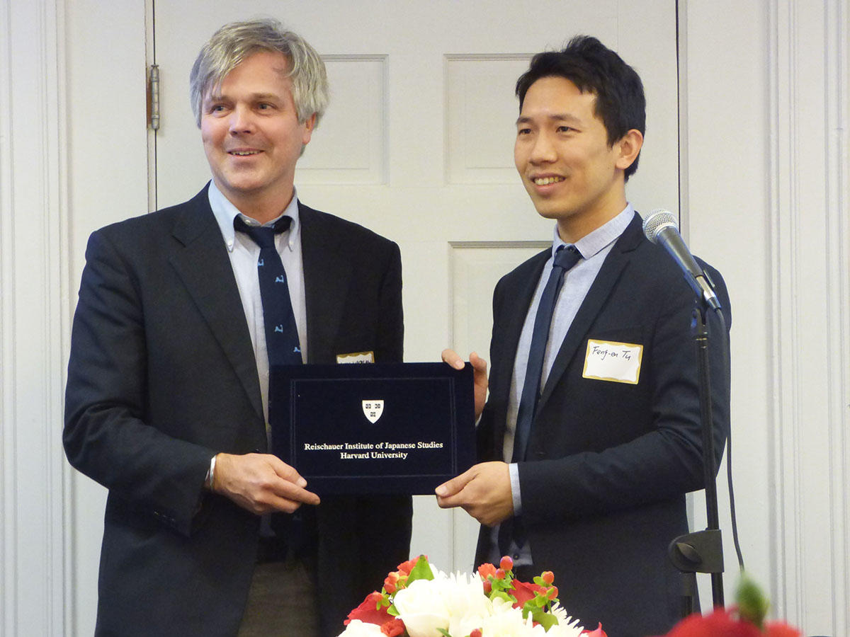 Gavin Whitelaw, left, and Feng-en Tu, right, hold up an embossed black folder containing the Noma-Reischauer Prize certificate between them