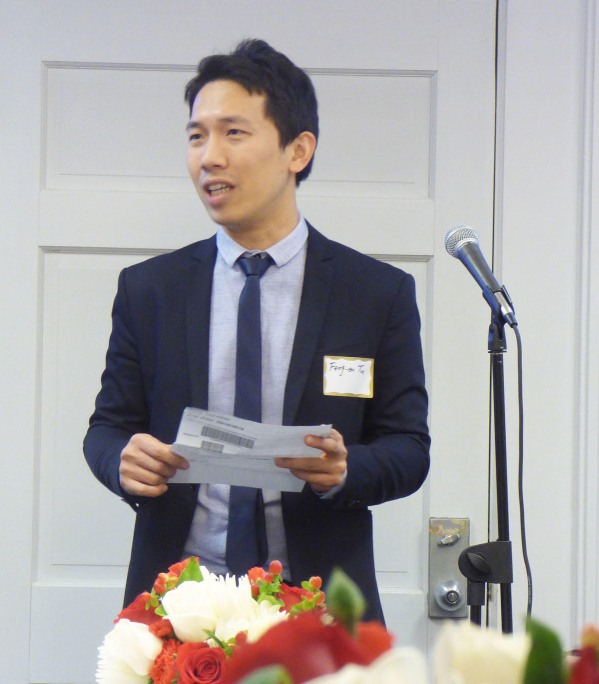 Feng-en Tu, wearing a dark suite and holding the prize certificate, delivers his speech in front of a microphone