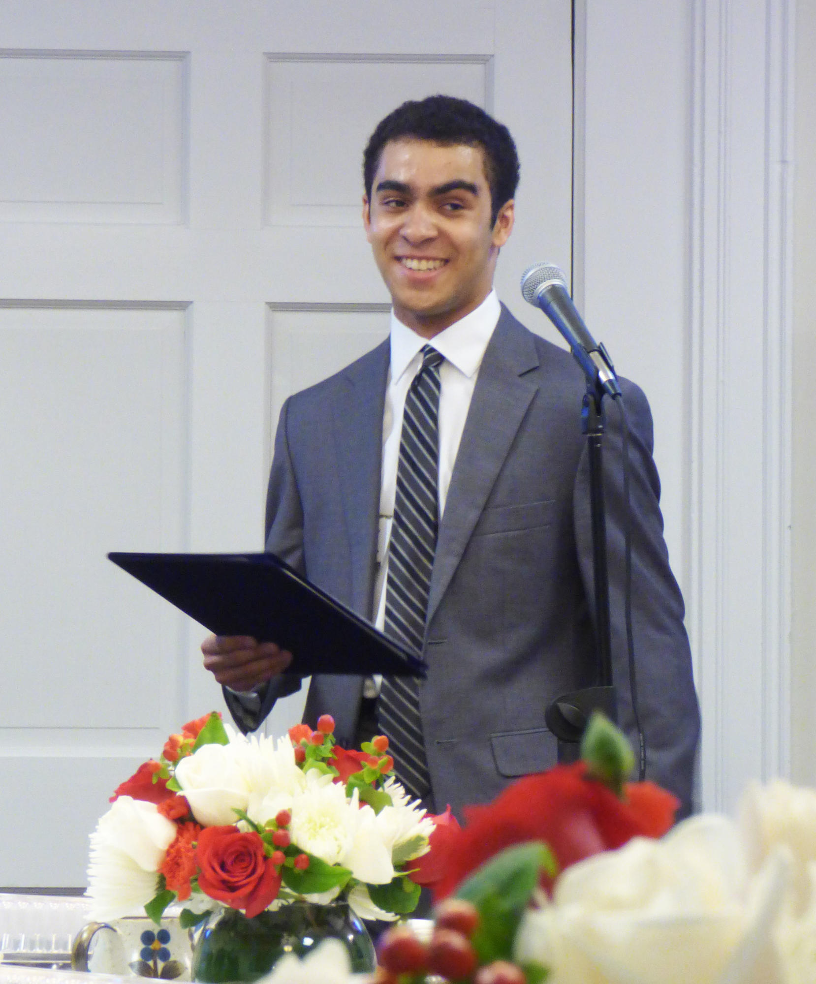 Devon, wearing a dark-colored suit, smiles as he stands in front of the microphone.