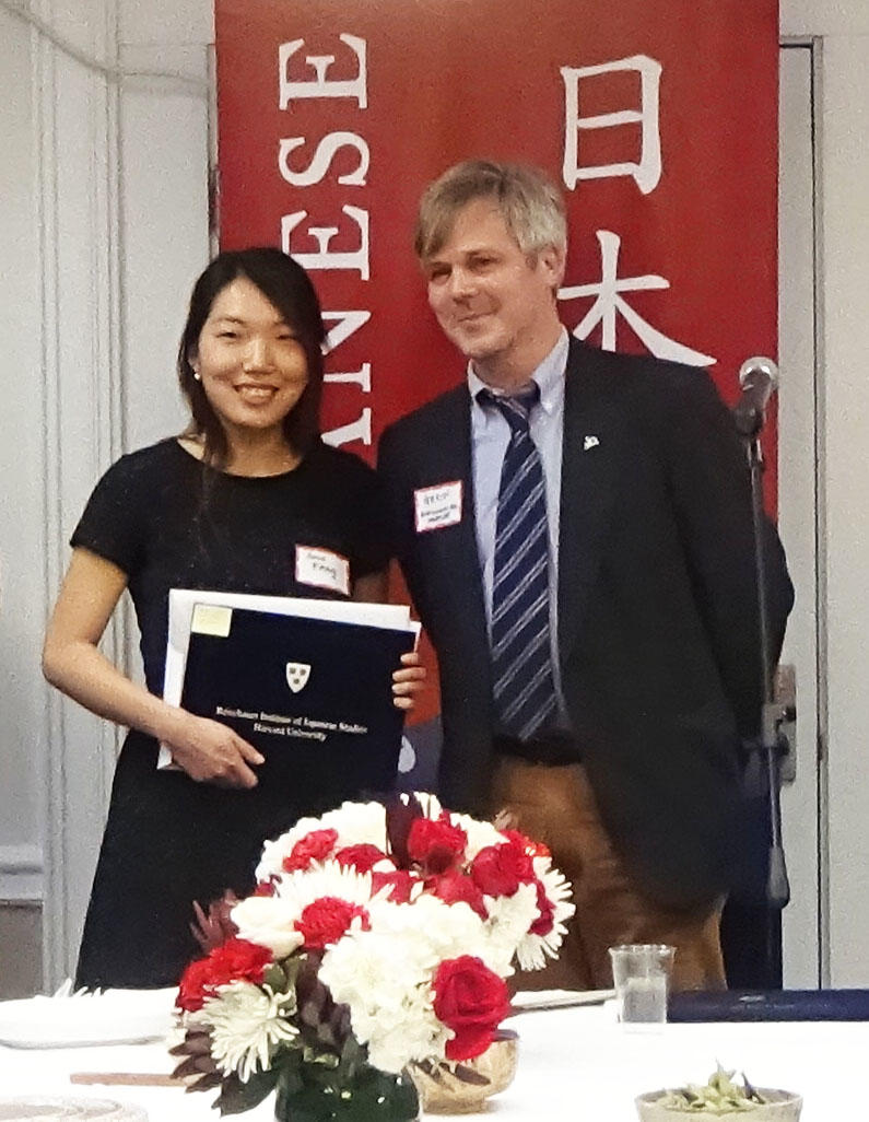 Sara Kang and Gavin Whitelaw stand side by side and smile at the camera. Kang is holding her Noma-Reischauer award.