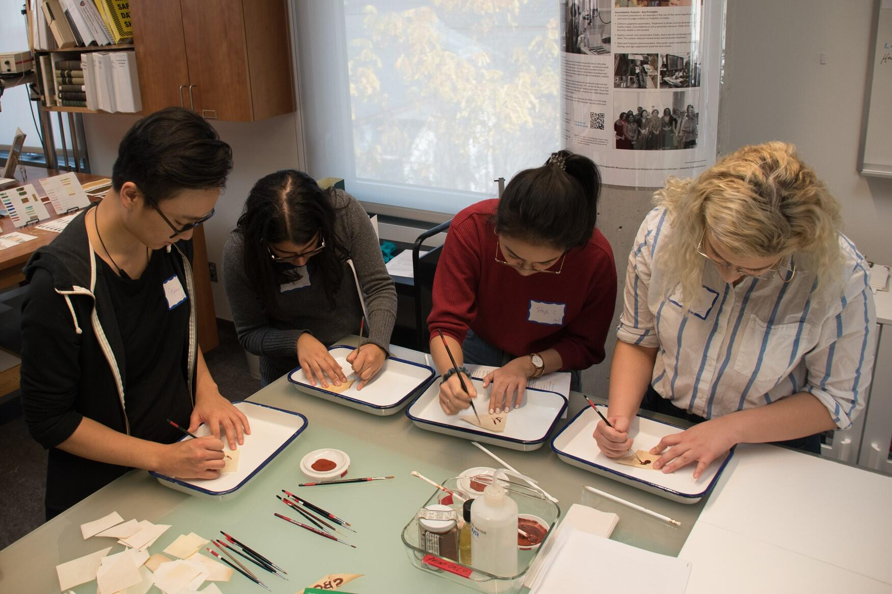 Students painting on small fragments of paper during a field trip to the Weissman Preservation Center.