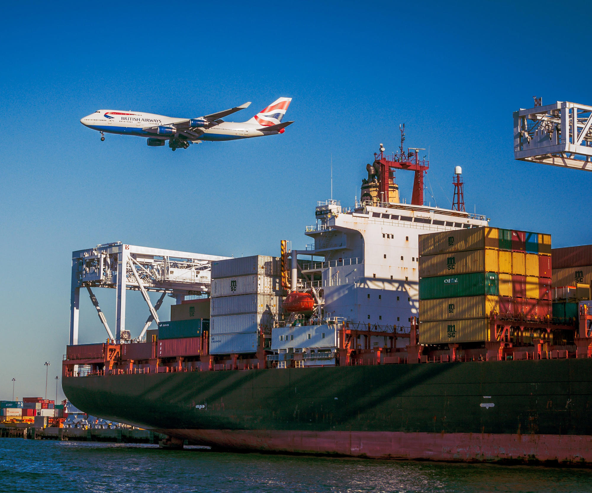 plane above shipping boat with crates
