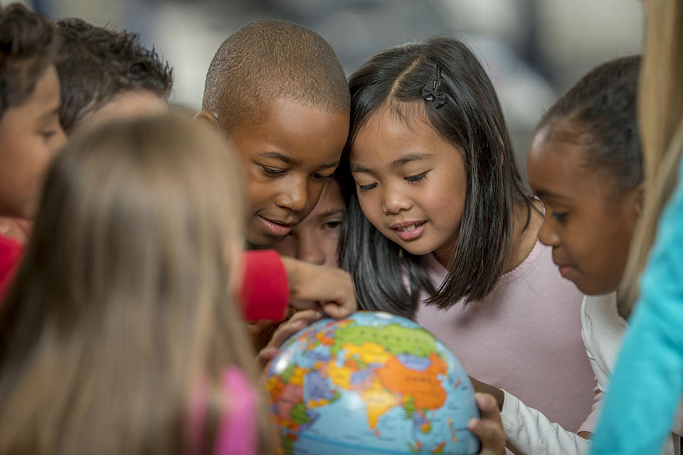 children gather around a globe