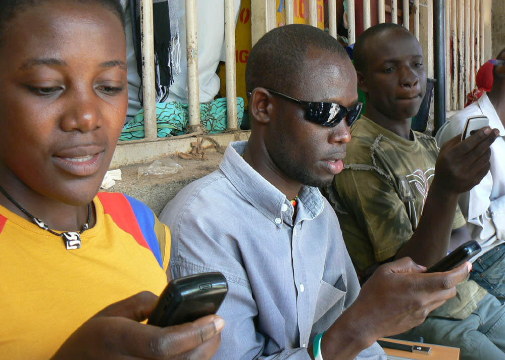 a row of people seated on a bench in Uganda, looking at and texting on their mobile phones