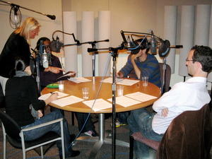 Image of three people sitting at the round table with microphones, in the studio