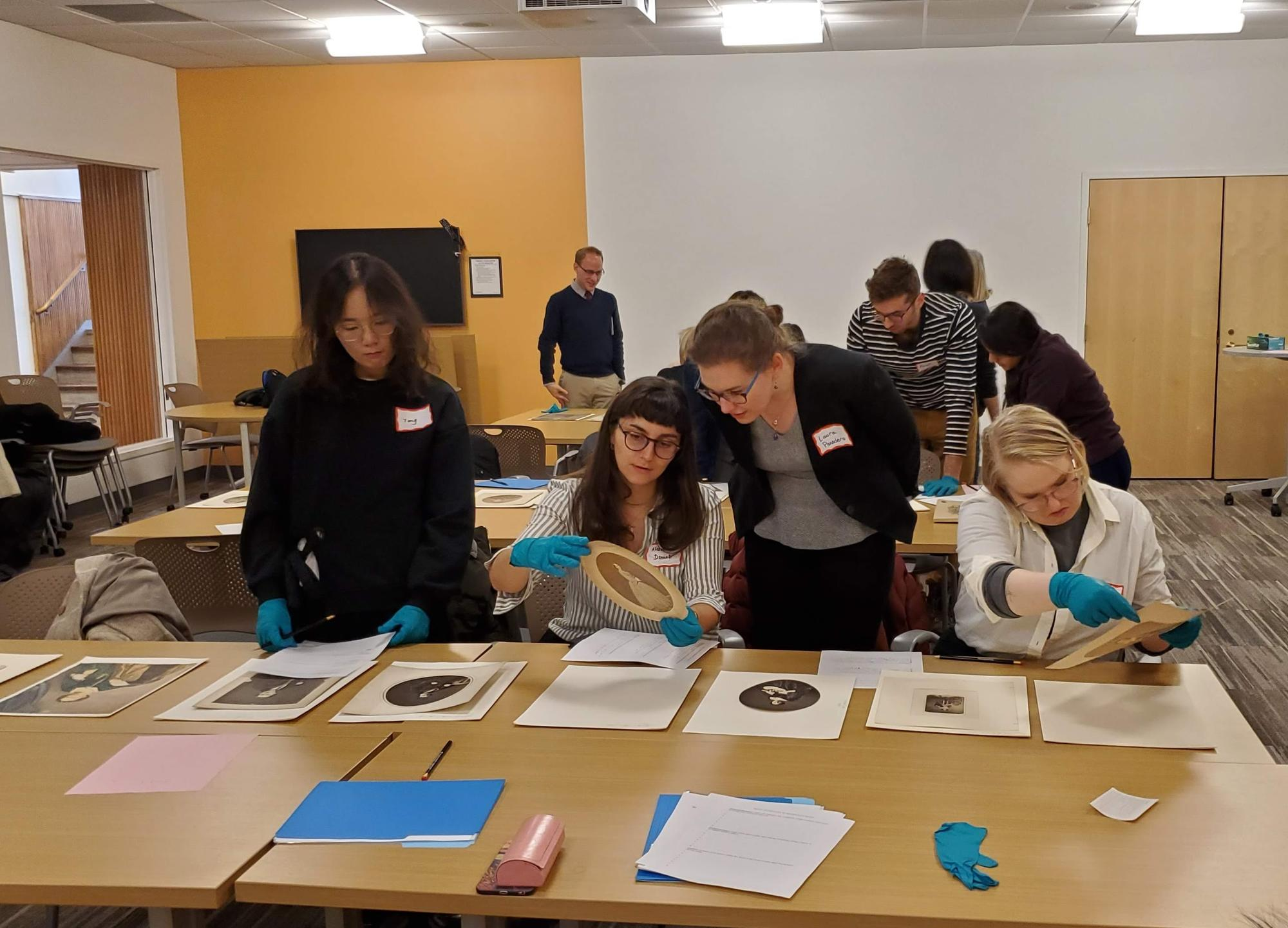 Students gathered around a table looking at salted paper prints.