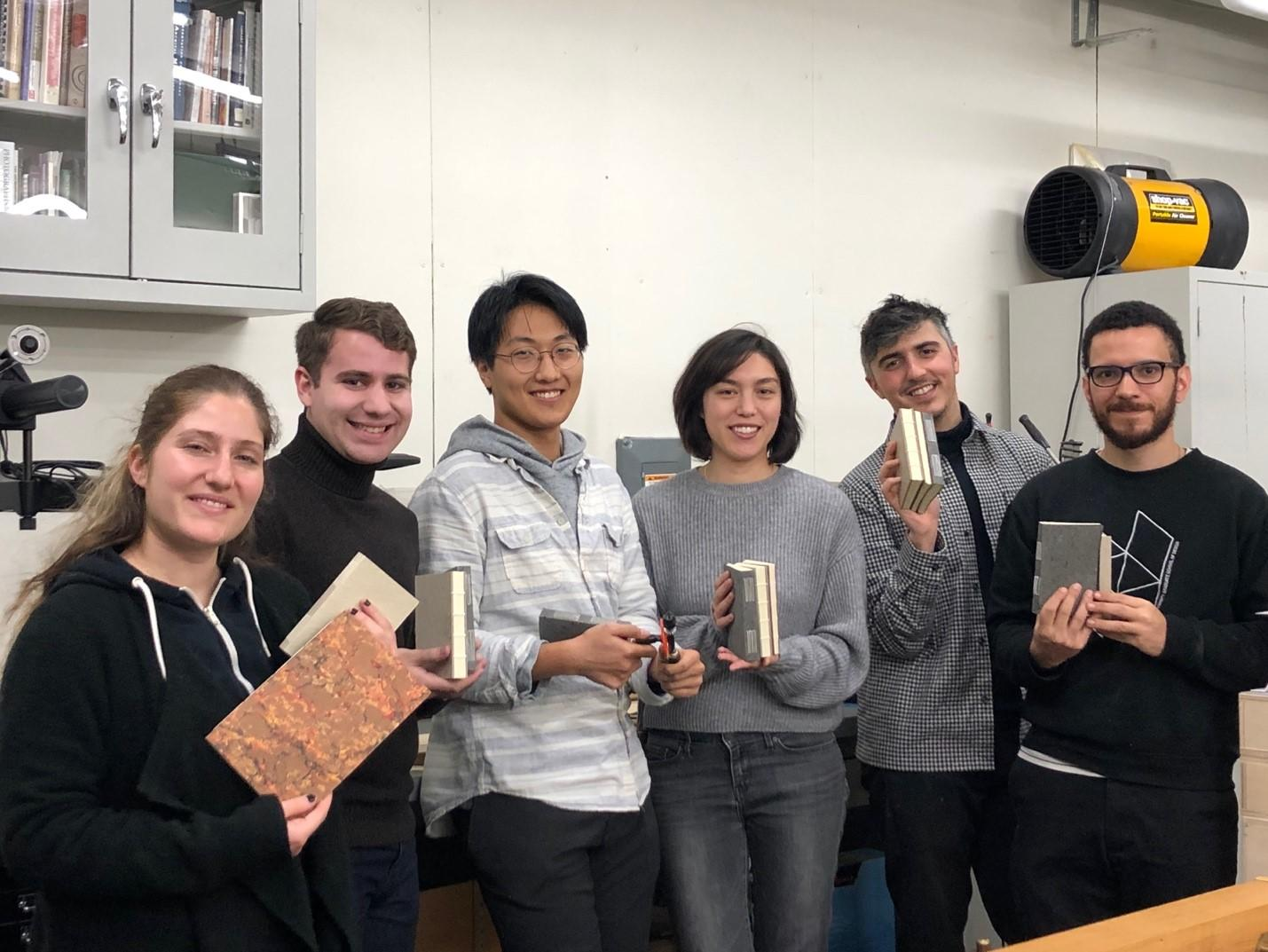 Students holding the books that they made in the workshop.
