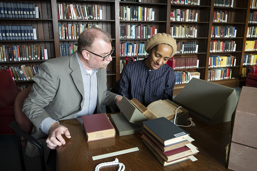 librarian and visitor looking at special collections materials