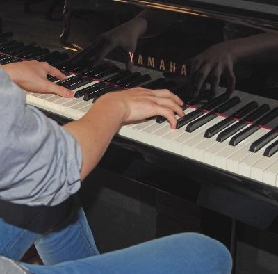 Male freshman student playing on his loaned piano in his dorm room