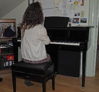Female freshman student composing at her loaned piano in her dorm room