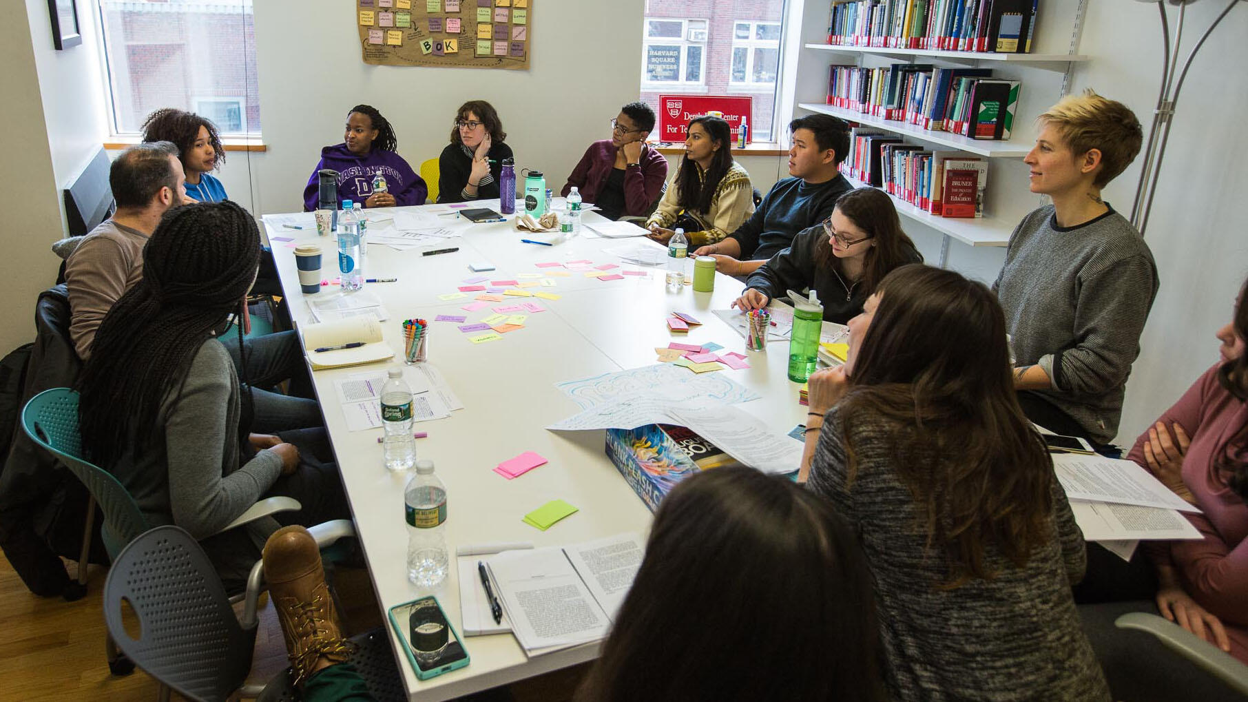 A group of undergraduate student fellows and graduate student fellows sit around a white rectangular table with colored cards and printed readings scattered around