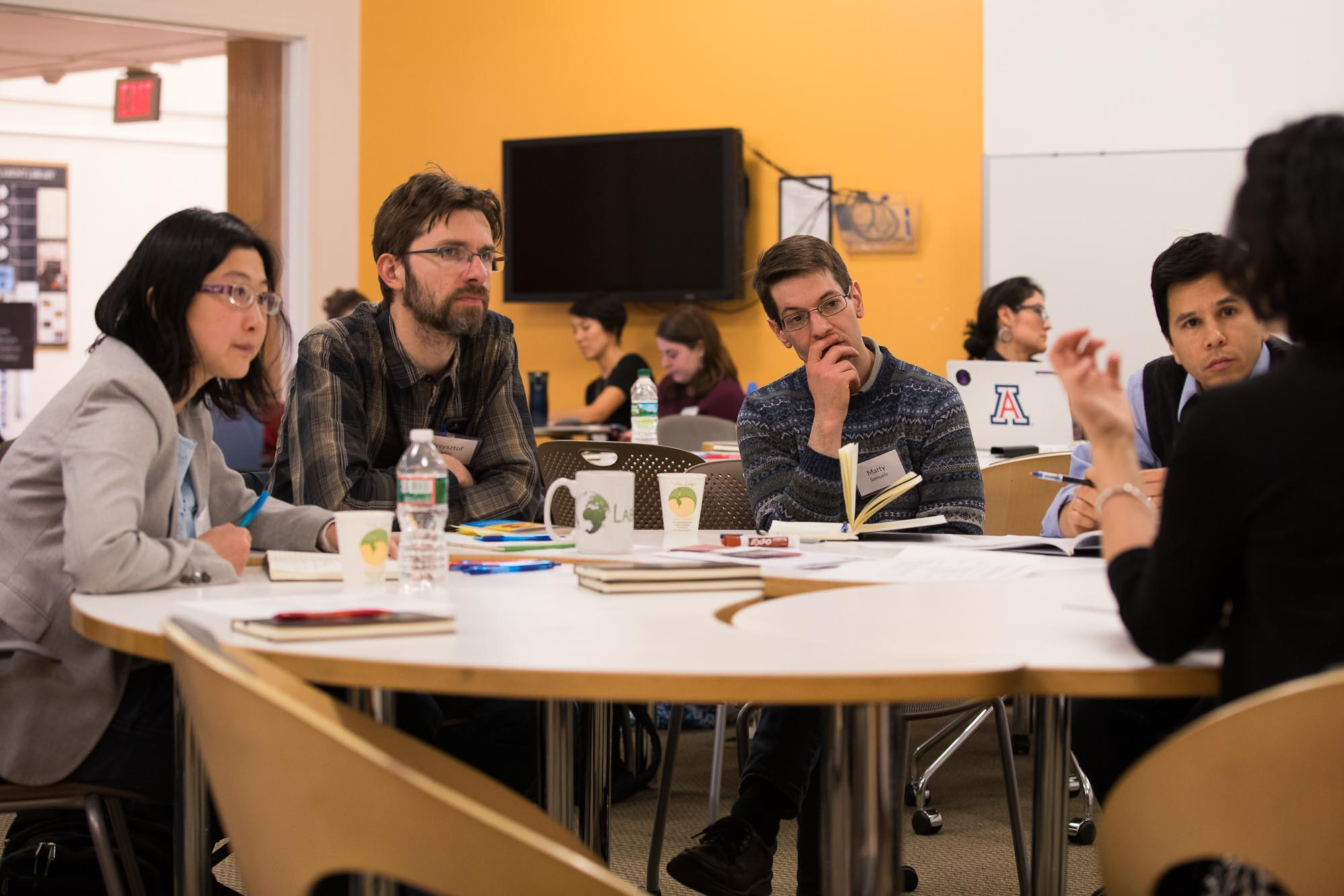 Faculty and staff sit around a circular table discussing teaching at a seminar