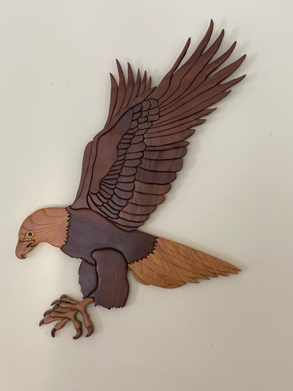 Carved wooden eagle in flight with talons extended.