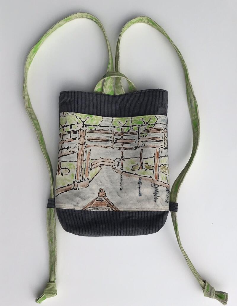 Handmade canvas backpack, with painted front panel with a landscape scene with trees in the background and a river and bow of boat in foreground. The bag has green straps.