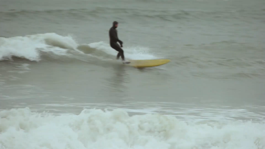 A man in a black wetsuit surfs and crashes along the waves of a grey sea.