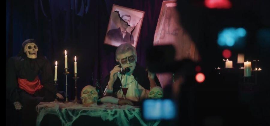 A man talks sadly into the phone behind a camera, dressed in a vampire suit and face painted. The dark room is lit by burning candles and spooky Halloween decorations.