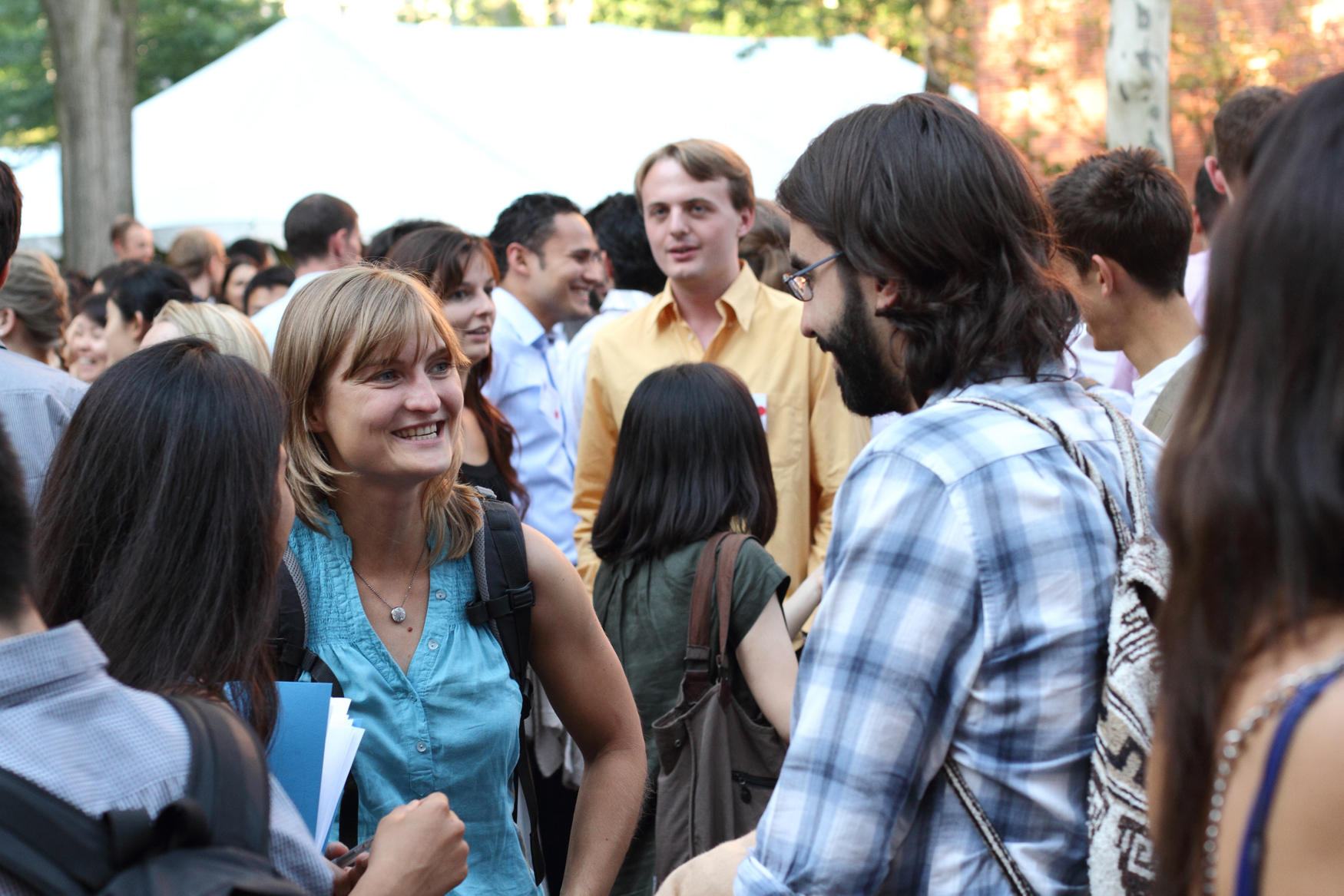 Two researchers mingle at an outdoor social event