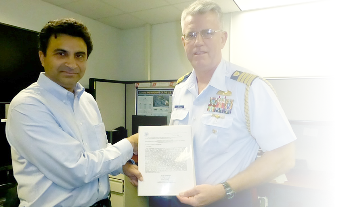 Professor Tambe receives an award from the Commandant of the US Coast Guard