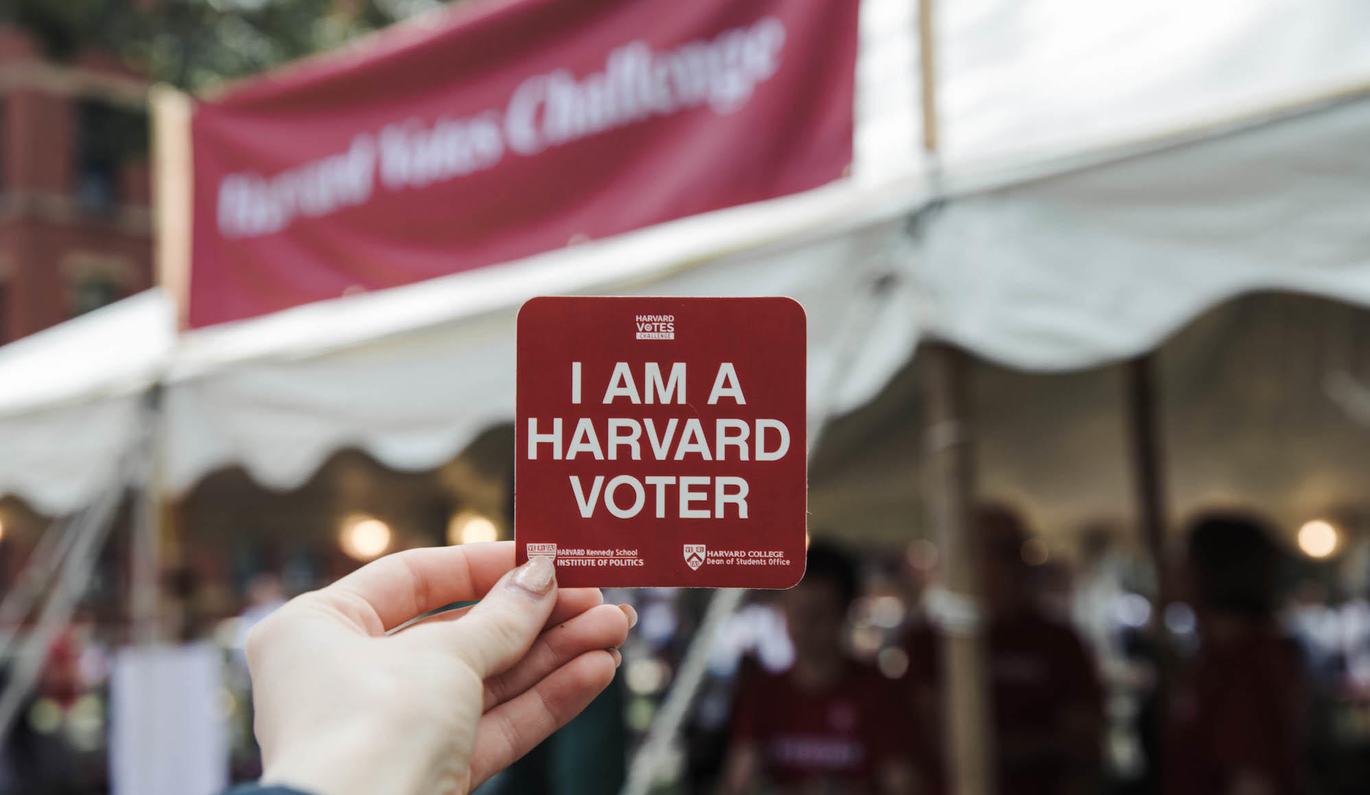 "Person holds an ""I am a Harvard Voter Sticker"""