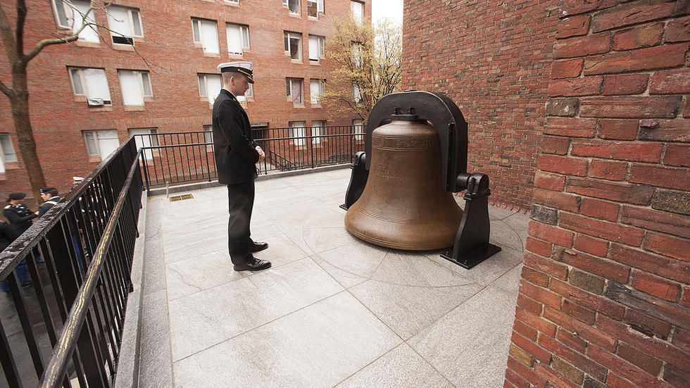 Midshipman Mike Murray '17, takes a moment to honor the bell cast in 1926 to honor those in the Harvard community who sacrificed their lives in World War I.