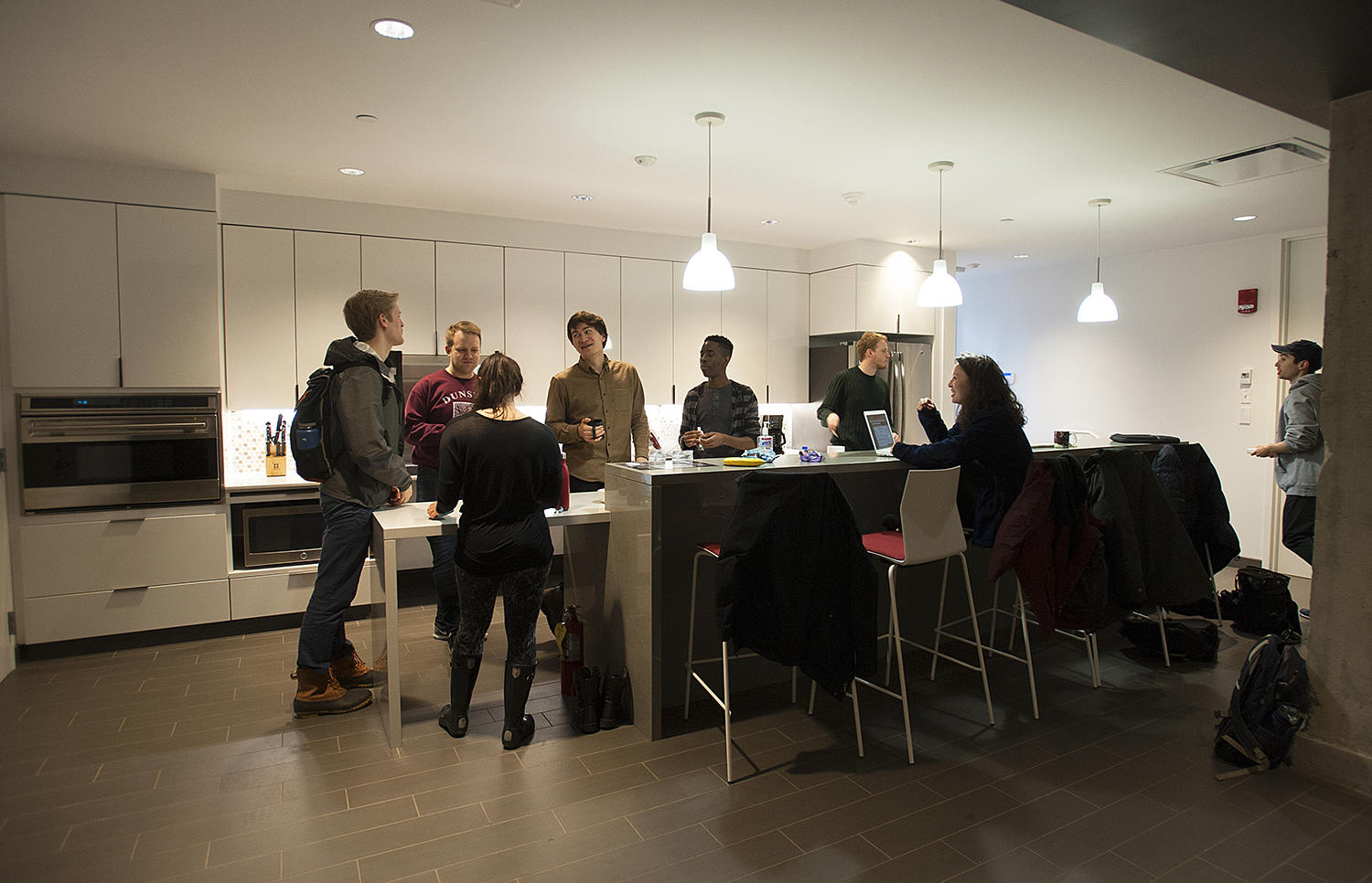 Members of the Harvard University Choir socialize in the new kitchen before rehearsal