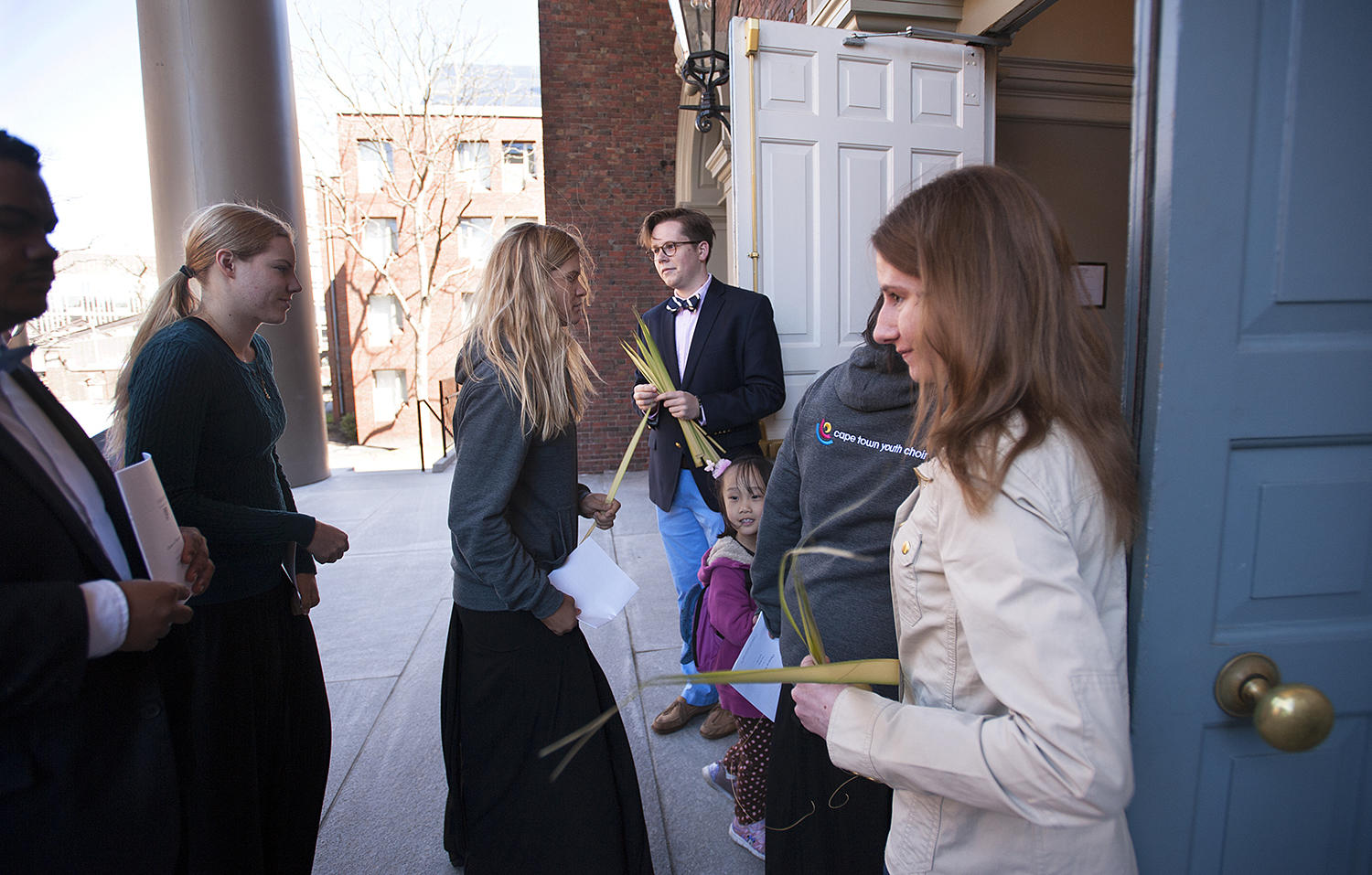 Student deacons hand out palms to the congregation on Palm Sunday