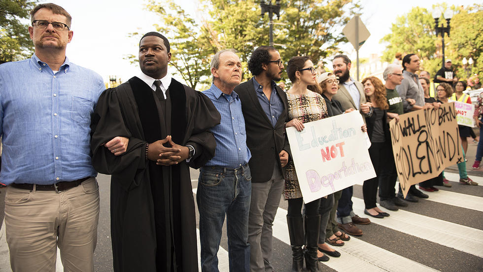 Prof. Jonathan L. Walton along with other local educators blocks traffic during protest