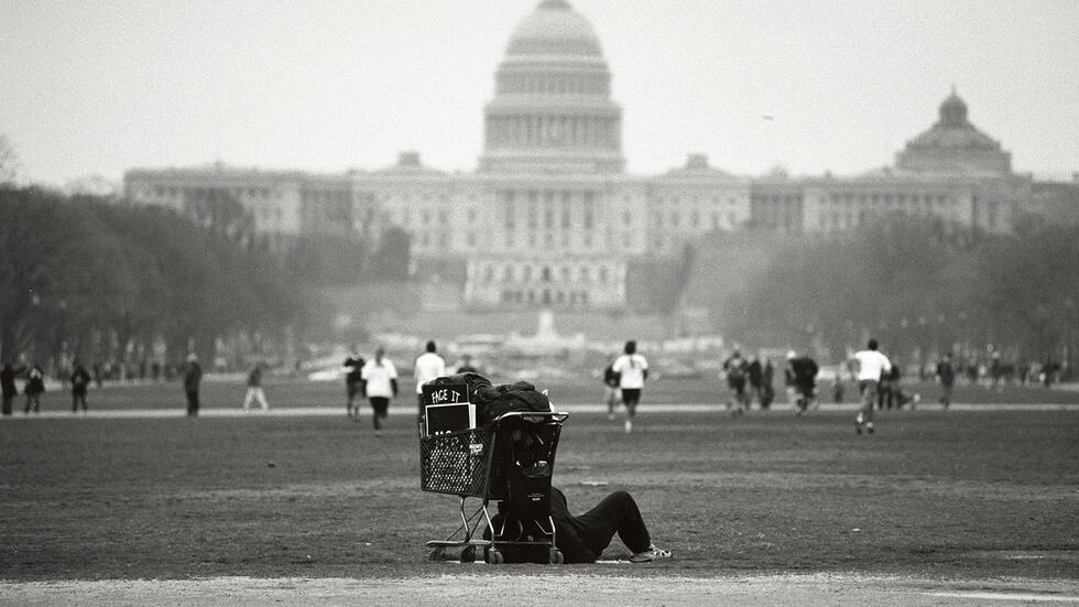 Homeless man in the shadow on the U.S. Capital