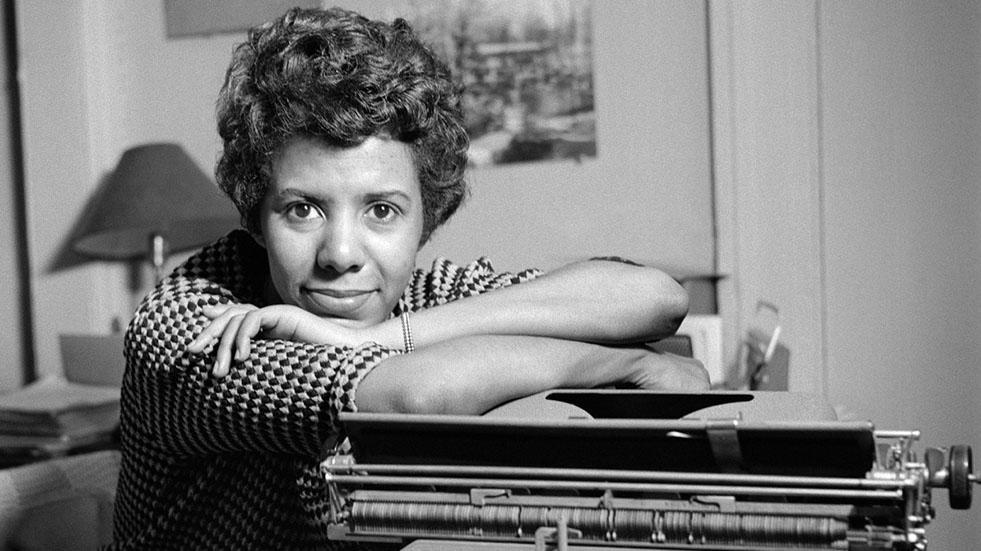 Photo of Lorraine Hansberry seated at a typewriter