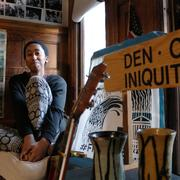 Eden H. Girma in room with a sign that says Den of Iniquity