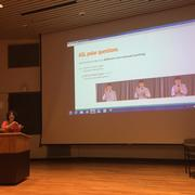 Aurore stands at a podium in front of a screen giving our NELS talk