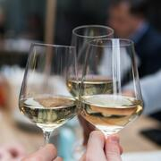 "three glasses of white wine touching in ""cheers"""