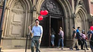 Jihwan Lee with balloons on steps of Memorial Hall