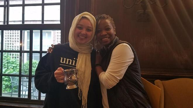 Two women smiling. One is wearing a hijab holding a tankard. The other leans on the first woman's shoulder