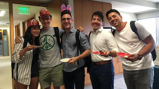 five students wearing Elmo hats and bunny ears smile at the camera