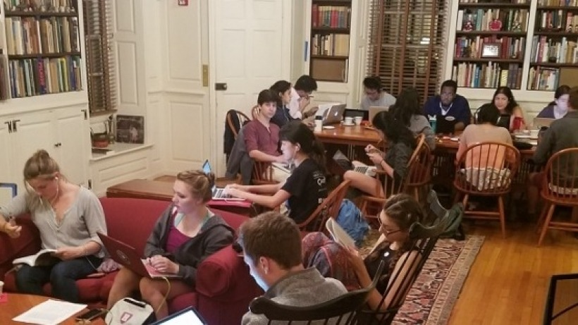 Mixed gender groups of of students studying at two different tables in a large room. Some are looking at the camera and some aren't.