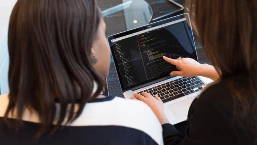 Two women looking at code on a laptop.