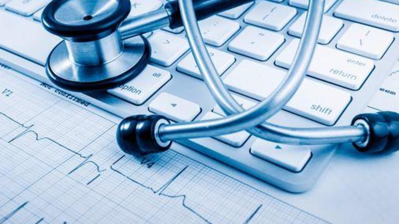 Black and white computer keyboard with stethoscope and graph.
