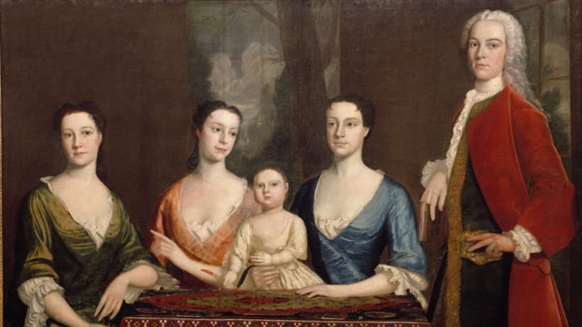 Group portrait of three women, a child, and a man standing on the right.