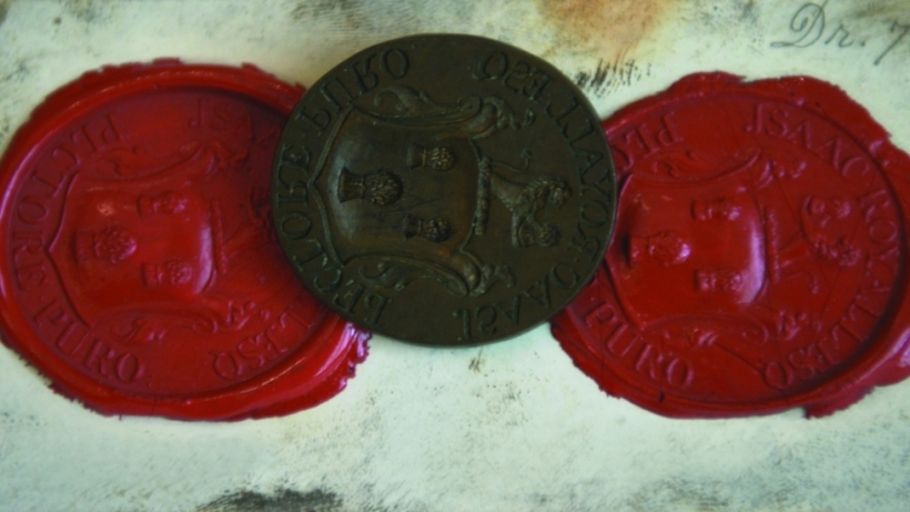 One iron seal in between two red wax impressions