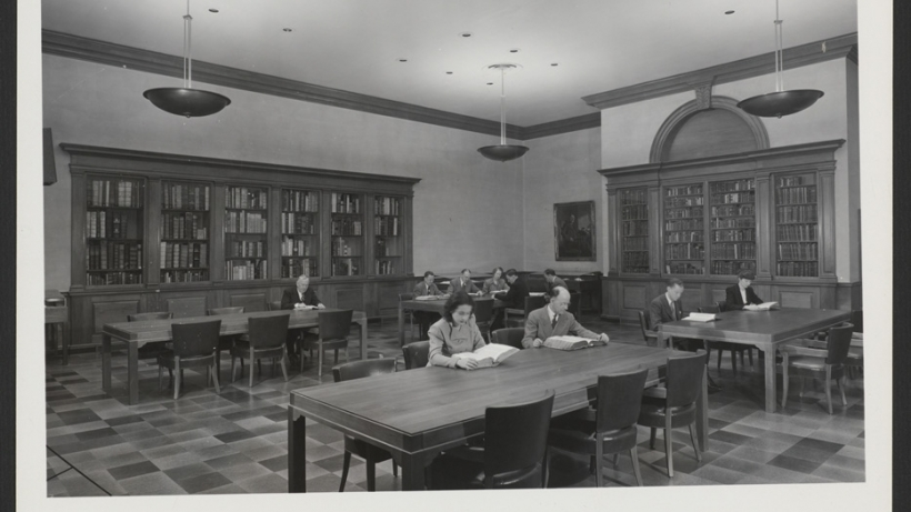 View of the Treasure Room, Langdell Hall with men and women sitting at tables. Bookcase pediment is blank, prior to the addition of the painted shield.