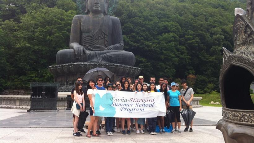 "Image of HSS Korea Program students holding an 'Ewha-Harvard Summer School Program"" banner in front of a bronze Buddha statue at the Sinheungsa Temple inside Mount Seoraksan in Sokcho-si, Gangwon-do, South Korea"