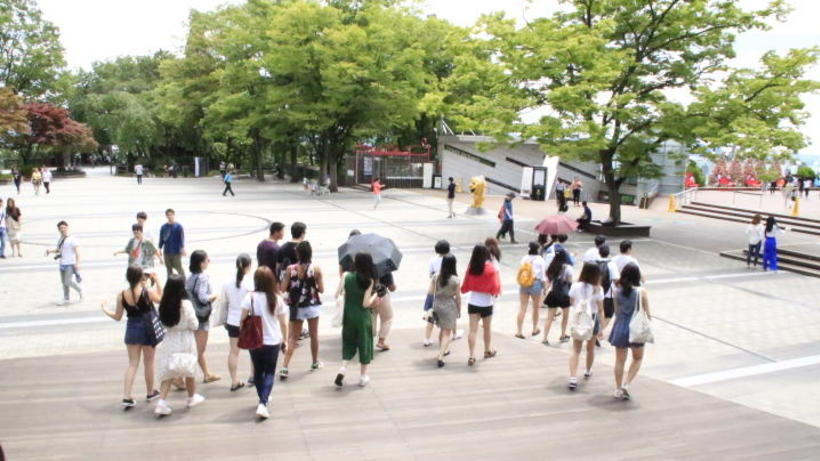 Image of 2018 HSS Korea Program students walking across a park on a sunny day in South Korea