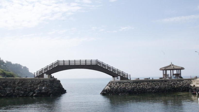 Image of a traditional bridge and pagoda by the ocean in South Korea visited by the 2019 HSS Korea Program