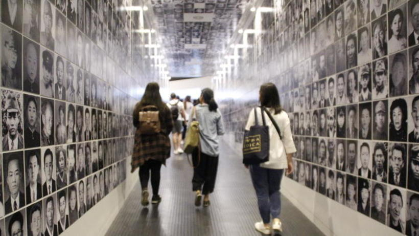 Image of students on 2019 HSS Korea Program on a fieldtrip walking through a gallery, displaying black and white pictures of historical Korean figures, in South Korea
