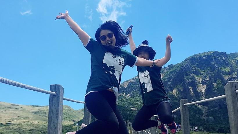 Image of two 2019 HSS Korea Program students jumping at a mountain trail on an excursion on a sunny day in South Korea