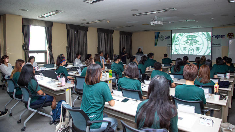 Image of 2019 HSS Korea Program students listening to a historical presentation in a classroom at Ewha University