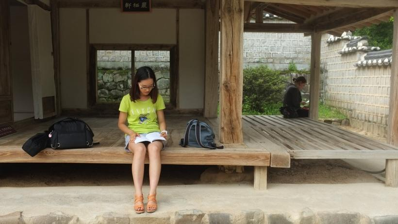 Image of a student in HSS Korea Program reading a book while sitting at the edge of a traditional 'hanok' building in South Korea