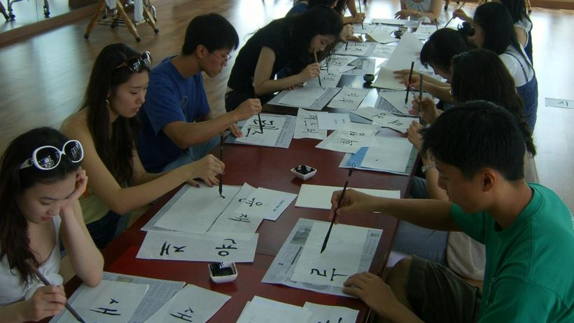 Photo of HSS Korea Program students at a table practicing Korean Hangul calligraphy